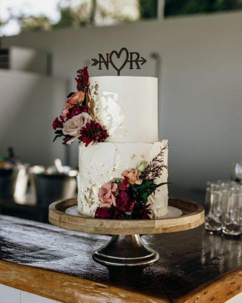 biały tort weselny z ciemnymi kwiatami