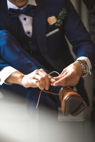 mężczyzna w garniturze wiąże buty
